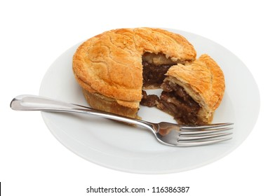 Meat pie and a fork on a plate isolated against white