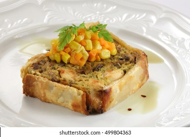 Meat pie piece served with corn and carrot
