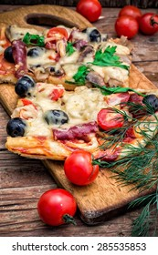 meat pizza made with salami,cheese,mushrooms,cherry tomatoes and olives.The image is tinted.