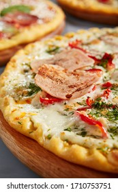 Meat pizza on wooden board. Bakery with ham, chicken, salami, tomatoes, bell pepper, mozzarella and white sauce close up. Traditional italian food, served restaurant meal, hot snack