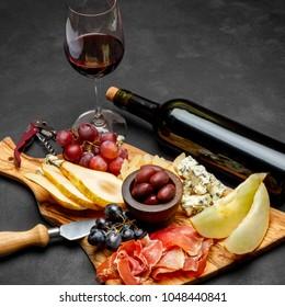 Meat plate antipasti snack - Prosciutto ham, blue cheese, melon, grapes, Olives