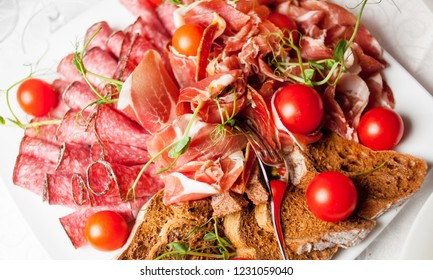 meat plate. Food tray with delicious salami, pieces of sliced ham, sausage, cherry tomatoes and brown bread - Meat platter with selection - Cutting sausage and cured meat on a celebratory table.