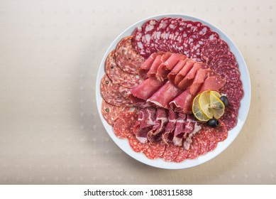 Meat plate set with salami, bacon, hamon on a white.