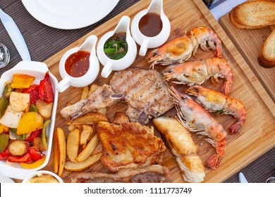 Meat platter served with salad, fries and red wine with three choice of sauce on wood block at fine dining table set.