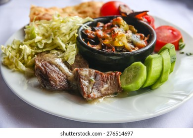 Meat in a  pot with tomato and cucumber