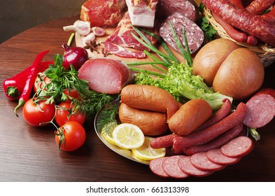Meat products and vegetables on wooden table.
