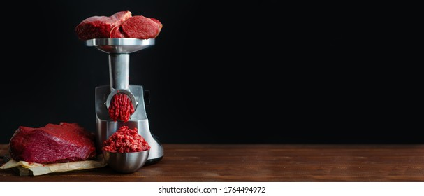 The meat is put in the meat grinder and minced  comes out of it, next to it lies a huge piece of beef tenderloin. Minced meat, meat delicacies, fresh craft food. Elongated panoramic image
