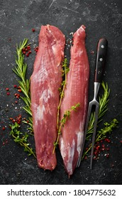 Meat. Raw pork tenderloin with spices on a black stone background. Top view. Rustic style.