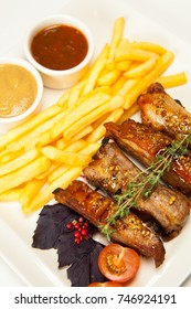 Meat ribs with french fries on white plate
