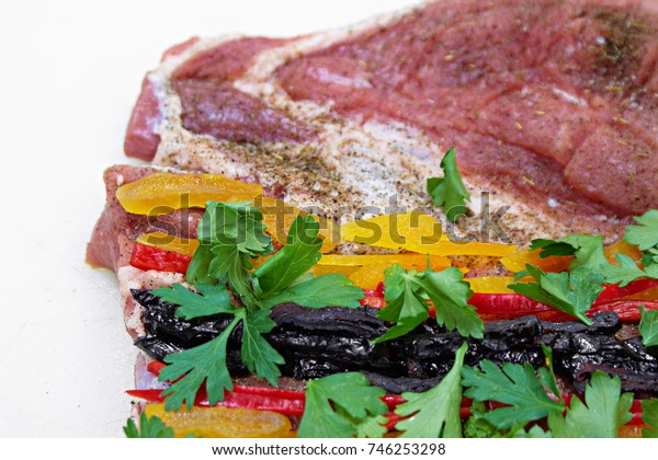 meat roll with prunes, dried apricots, chili peppers and spices on white background