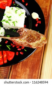 meat savory: roast veal ribs with rice garnish and pomegranate seeds on black over wood