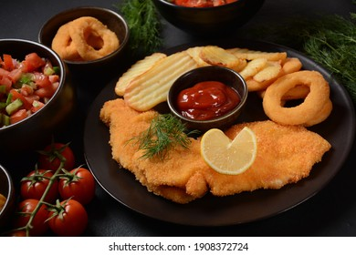 Meat schnitzel and fried potatoes with onion rings deep fried, vegetable salad