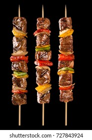 Meat skewer with vegetables on a black background. Paulistinha.