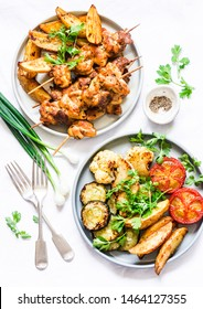 Meat skewers kebab with baked potatoes and roasted zucchini, tomatoes, cauliflower on a light background, top view. Delicious tapas, appetizers in mediterranean style