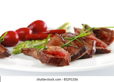 meat slices on white with asparagus on plate