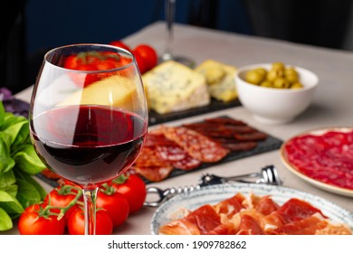 Meat slicing and wine on gray background