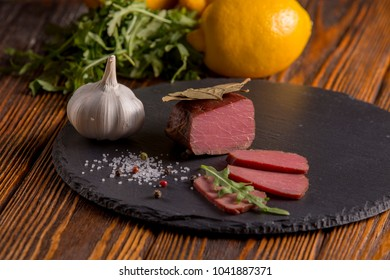 Meat with spices and rucola on a wooden table