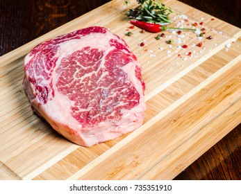 meat steak with blood on a wooden cutting board