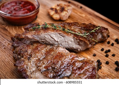 Meat steak on a wooden board with vegetables
