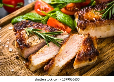 Meat steaks with fresh salad served at wooden board. Close up