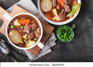 Meat stew with beef, potato, carrot, pepper, spices, green peas. Slow cooked meat stew, bowl, wooden background. Hot autumn/winter dish. Closeup. Top view. Comfort food. Homemade soup/ragout/casserole