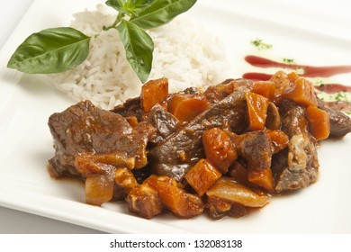 Meat stew with plain rice on a white plate