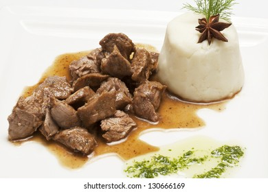 Meat stew (pork or beef) with side dish on a white plate