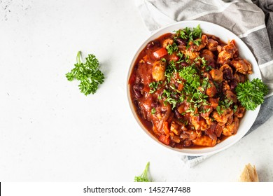 Meat stew with red beans, bell pepper and onion in tomato sauce in a white plate over light grey slate or stone background.