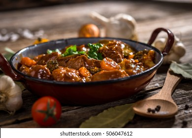 Meat stew with vegetable on rustic wooden background