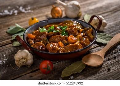 Estofado de carne con verduras sobre fondo rústico de madera