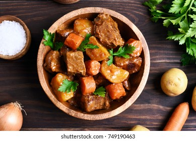 Meat stew with vegetables in bowl on wooden background, top view