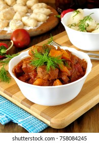 Meat stewed in tomato sauce. Porkolt, Hungarian cuisine meal. Gnocchi, a type of dumplings in the background