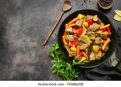 Meat stewed with vegetables in a black bowl over dark slate,stone or metal background.Top view with copy space.