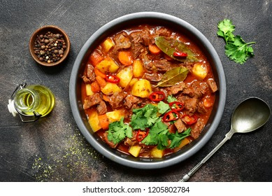 Meat stewed with vegetables in tomato sauce (hungarian goulash) in a vintage plate over dark blue slate,stone or concrete background.Top view with copy space.