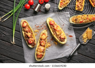 Meat stuffed zucchini boats and vegetables on wooden table