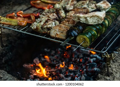 Meat and vegetable shish kabobs grilling on fire with flames. Barbecue in tourist forest camp. Concept - healthy food.