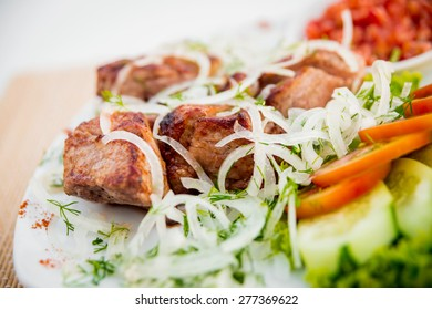 Meat with vegetables on a white plate. Restaurant