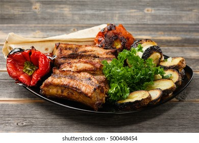 The meat and vegetables roasted on a grill with greens   black plate in style  rustic