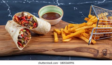 Fleischverpackung; Türkischer Name, Et Durum. Tortilla-Packungen mit zart geschnittenem, geröstetem Steak, rotem Chilischoten und Salatbeschneidungen auf dunklem Hintergrund mit Kopienraum