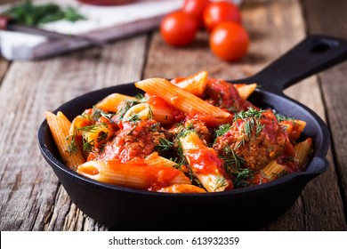 Meatball with penne pasta and spicy red sauce  in cast iron skillet on rural wooden table