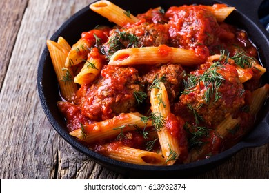 Meatball penne pasta with spicy tomato sauce and dill in cast iron pan on rustic wooden table