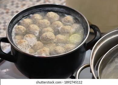 meatball soup boils in a saucepan