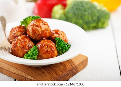 Meatballs with barbeque sauce and broccoli on wooden table.