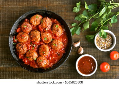 Meatballs in cast iron pan, fresh parsley and tomatoes on wooden table, top view