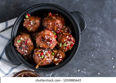 Meatballs cooked with teriyaki sauce in pot, ready to eat.