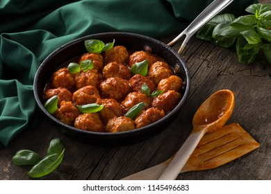 Meatballs in a frying pan with tomatoes, basil. Meatballs served on a old wooden table with green napkin and spoon.