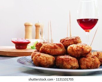 Meatballs on plate over the table with a glass of red wine, ketchup and tableware on light background.