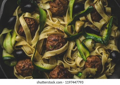 Meatballs on wooden skewers with pesto pasta