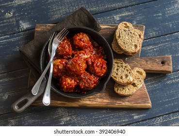 Meatballs in a pan on rustic wooden board