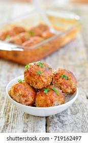 Meatballs in a plate decorated with greens. Wooden background. Vertical photo.
